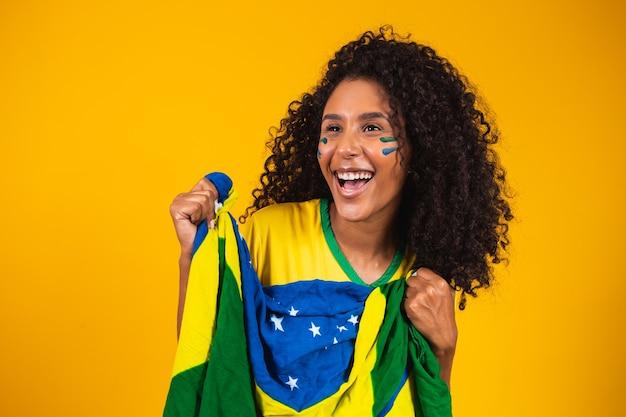Afro meisje juichen voor favoriete braziliaanse team, met nationale vlag op gele achtergrond.