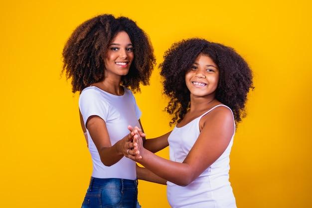 Afro moeder en dochter dansen op gele achtergrond