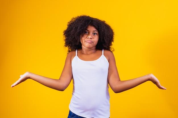Afro mooi meisje over verwarde uitdrukking en clueless geïsoleerde achtergrond met armen en opgeheven handen. twijfel concept.
