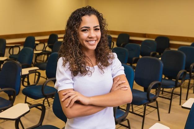 Afro student in de klas met gekruiste armen kijken camera glimlachen. jonge student met het klaslokaal op de achtergrond.