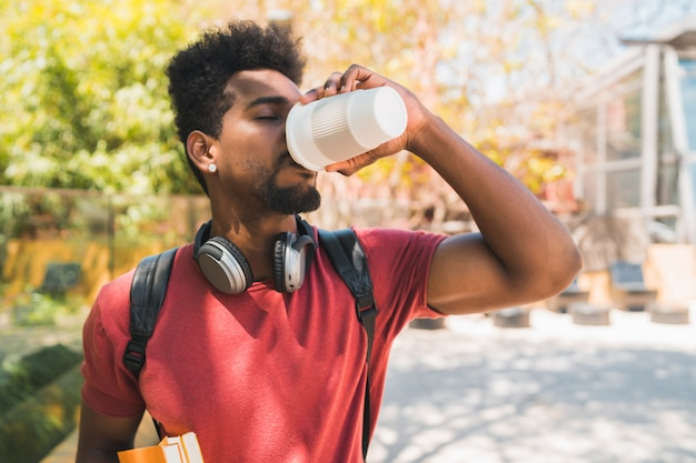 Afro universitaire student die een kop van koffie drinkt.