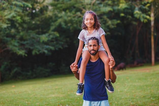 Afro vader en dochter in het park