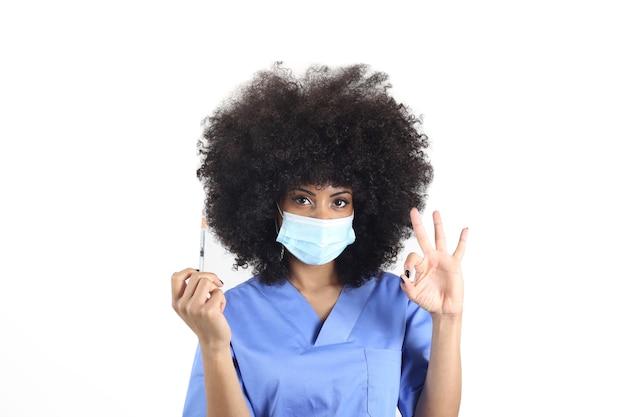 Afro-vrouw arts met medisch masker en spuit met vaccin, maakt ok gebaar
