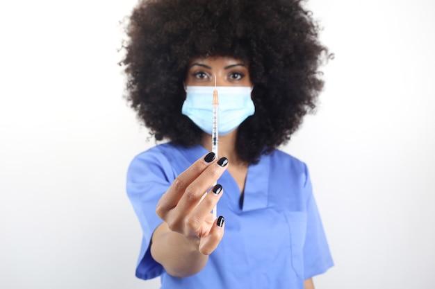 Afro-vrouw arts met medisch masker met spuit, covid-19 vaccinconcept