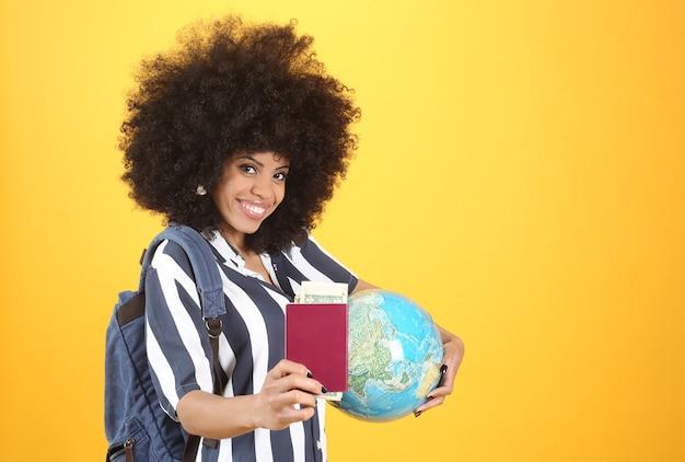 Afro-vrouw bereid om te reizen met paspoort, earth globe, rugzak, geld, vrijetijdskleding, gele achtergrond