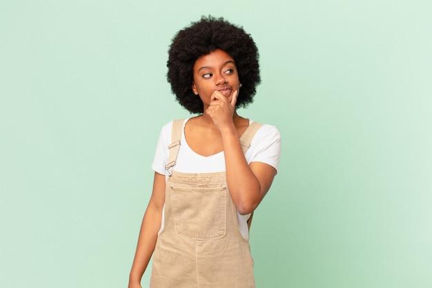 Afro-vrouw die denkt, zich twijfelachtig en verward voelt, met verschillende opties, zich afvragend welke beslissing ze het chef-concept moet maken