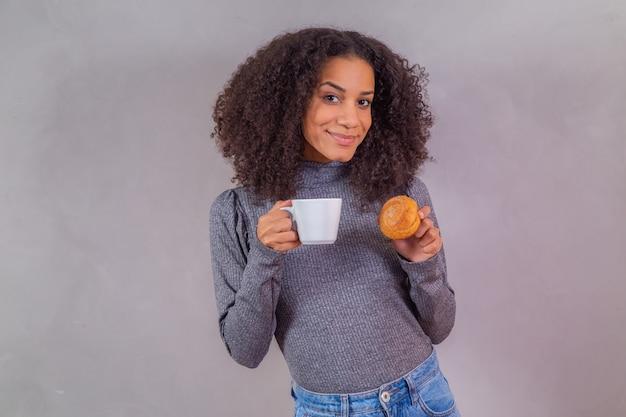 Afro-vrouw die donuts eet en koffie drinkt