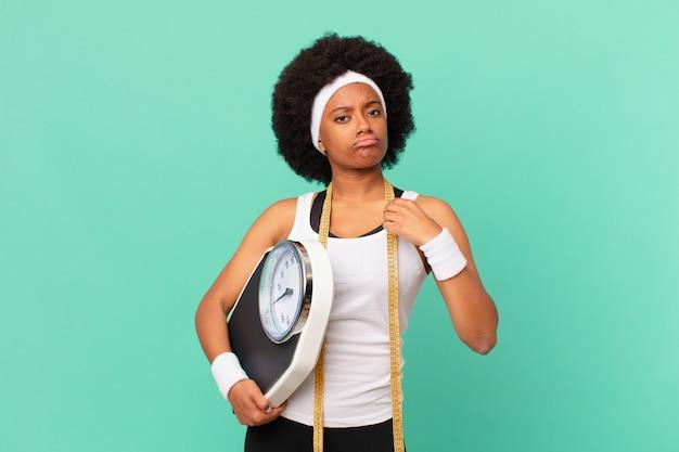 Afro-vrouw die er arrogant, succesvol, positief en trots uitziet, wijzend op zelfdieetconcept