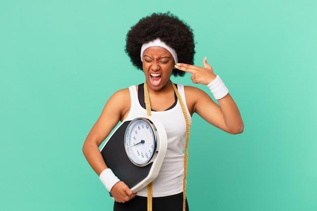 Afro-vrouw die er ongelukkig en gestrest uitziet, zelfmoordgebaar maakt een pistoolteken met de hand, wijzend naar het hoofddieetconcept