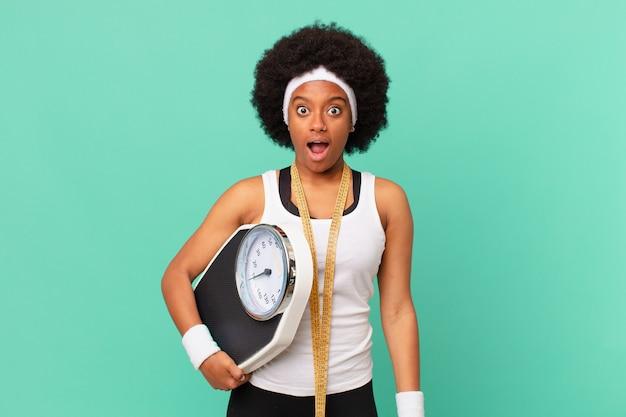 Afro-vrouw die erg geschokt of verrast kijkt, starend met open mond en zegt wow dieetconcept