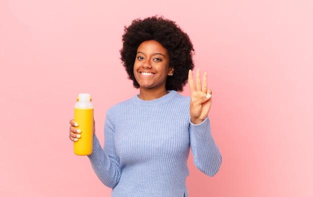 Afro-vrouw die lacht en er vriendelijk uitziet, nummer drie of derde toont met de hand naar voren, aftellend. smoothy concept