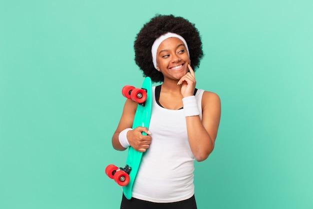Afro-vrouw die vrolijk lacht en dagdroomt of twijfelt, opzij kijkend. skateboard concept