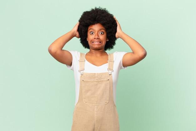 Afro-vrouw die zich gestrest, bezorgd, angstig of bang voelt, met de handen op het hoofd, in paniek bij het concept van de foutchef