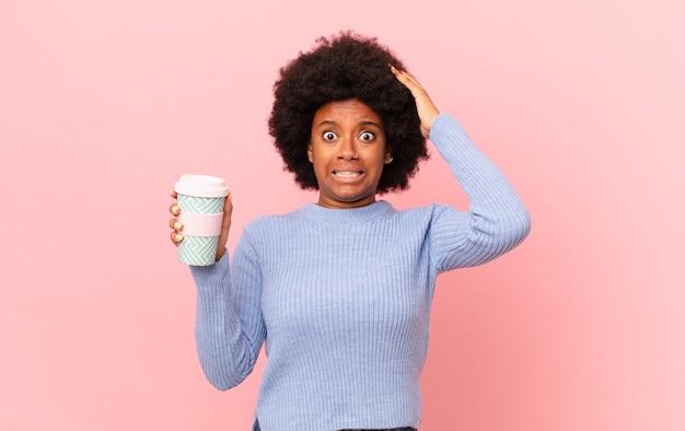 Afro-vrouw die zich gestrest, bezorgd, angstig of bang voelt, met de handen op het hoofd, in paniek per ongeluk. koffie concept