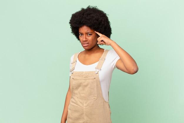 Afro-vrouw die zich verward en verbaasd voelt en laat zien dat je gek, gek of gek bent, chef-kokconcept