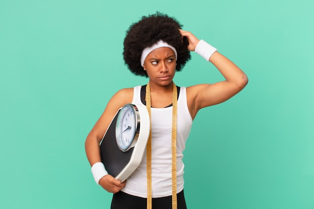 Afro-vrouw die zich verward en verward voelt, hoofd krabt en naar het zijdieetconcept kijkt