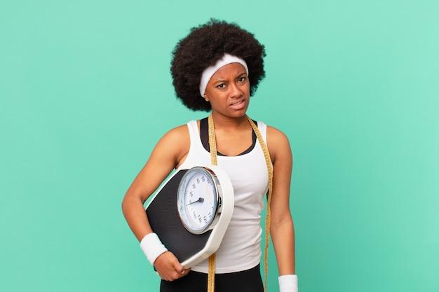 Afro-vrouw die zich verward en verward voelt, met een stomme, verbijsterde uitdrukking die naar iets onverwachts dieetconcept kijkt