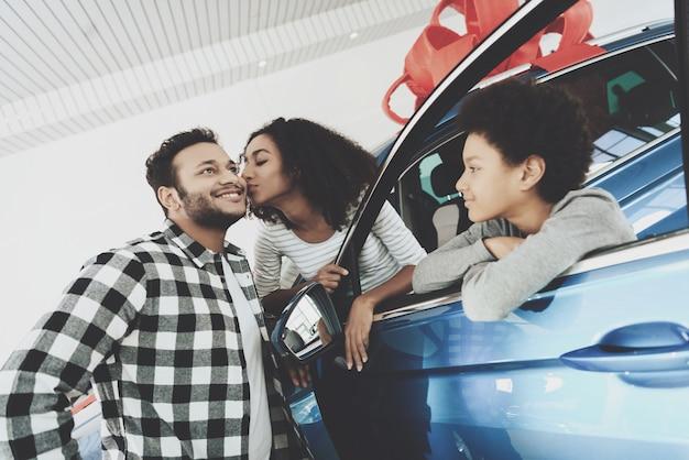 Afro-vrouw geeft kus aan echtgenoot voor cadeau-auto.