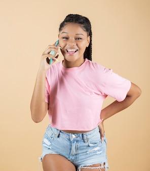 Afro-vrouw glimlacht terwijl ze telefoneert op gele achtergrond