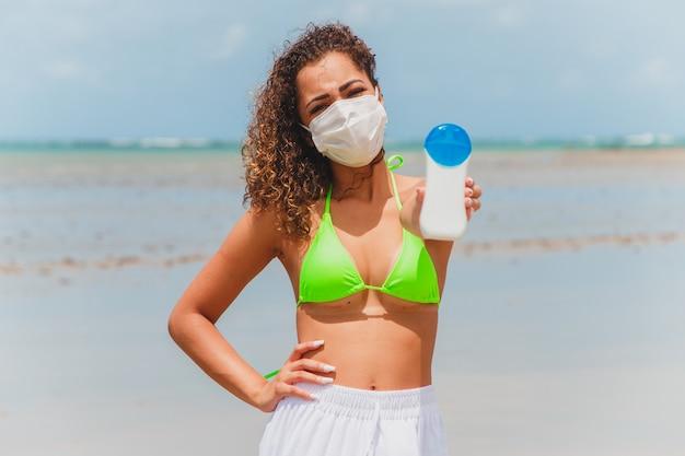 Afro vrouw in bikini en masker met zonnebrandcrème fles in de hand op het strand.