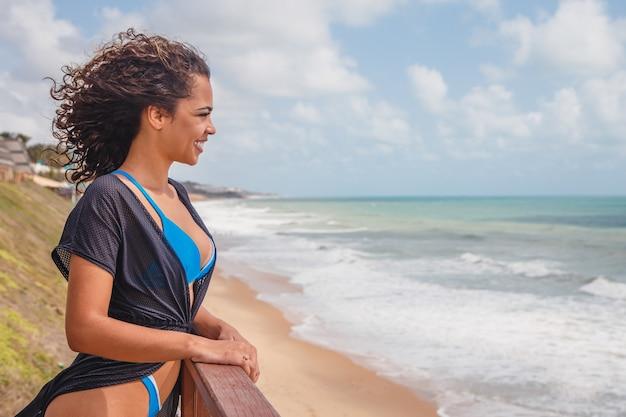Afro vrouw in bikini op strandvakantie.