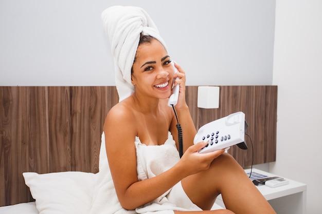 Afro-vrouw in handdoek die telefonisch in hotelkamer belt