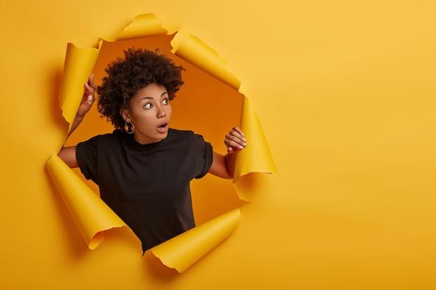 Afro-vrouw in zwart t-shirt hapt naar adem van verbazing, kijkt met angstige gezichtsuitdrukking opzij, gekleed in zwart t-shirt