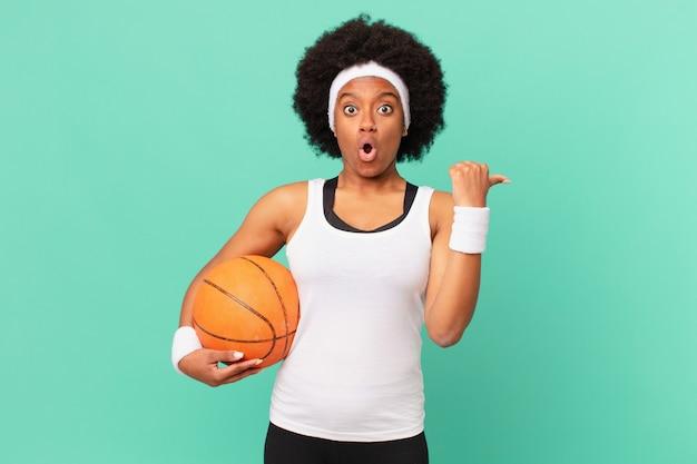 Afro-vrouw kijkt verbaasd in ongeloof, wijst naar een object aan de zijkant en zegt wow, ongelooflijk. basketbal concept