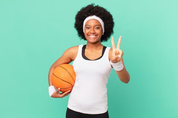 Afro-vrouw lacht en ziet er gelukkig, zorgeloos en positief uit, gebarend overwinning of vrede met één hand. basketbal concept