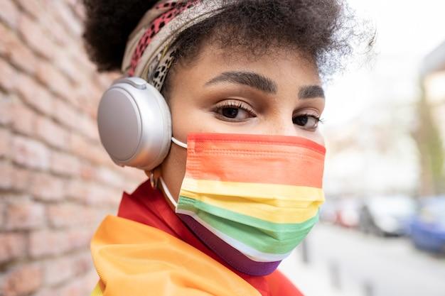 Afro-vrouw met gay pride-masker en koptelefoon