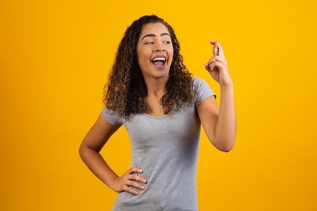 Afro-vrouw met gekruiste vingers juichende overwinning