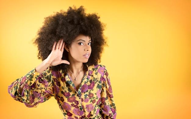 Afro vrouw met hand op haar oor, heeft gehoorproblemen, gele achtergrond