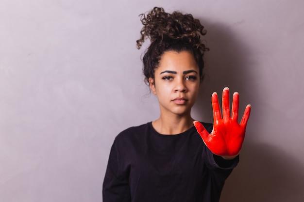 Afro-vrouw met handgeschilderd rood met stopconcept