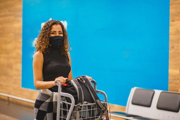 Afro vrouw met koffers op de luchthaven. vrouw op de luchthaven die in pandemie reist
