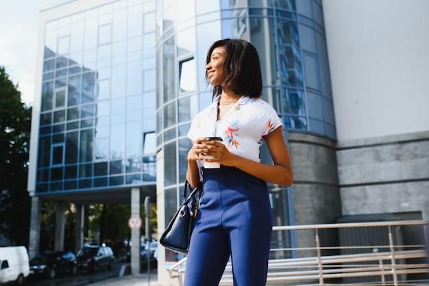 Afro vrouw met koffie om te gaan