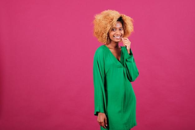 Afro-vrouw met krullend haar die naar de camera kijkt en glimlacht terwijl ze over een geïsoleerde achtergrond poseert.
