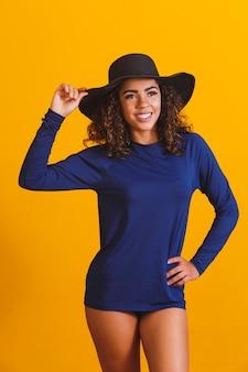 Afro vrouw met thermisch strand t-shirt en hoed