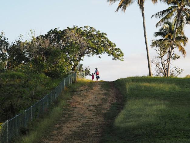Afro vrouw met zakken en een kind lopen op een landelijke weg in de ochtend. tropen omgeving. achteraanzicht