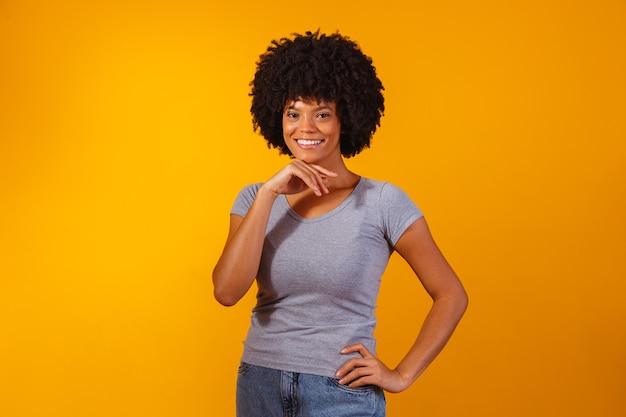 Afro-vrouw met zwart powerhaar dat lacht en naar de camera kijkt