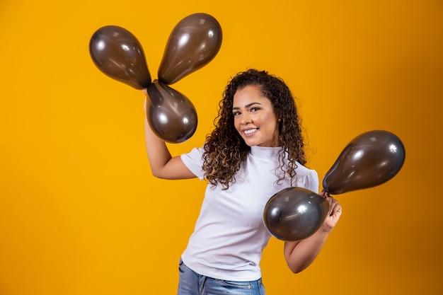 Afro-vrouw met zwarte ballonnen die verjaardagsaanbiedingen viert. black friday-uitverkoop