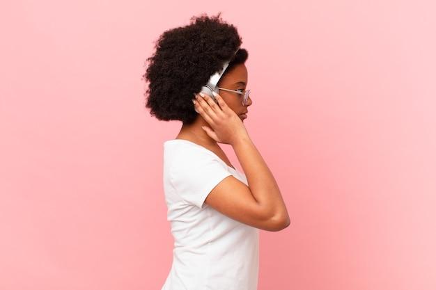 Afro-vrouw op profielweergave die ruimte vooruit wil kopiëren, denken, fantaseren of dagdromen. muziek concept