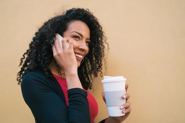 Afro vrouw praten aan de telefoon.