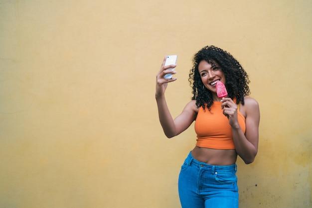 Afro vrouw selfies nemen met telefoon tijdens het eten van ijs