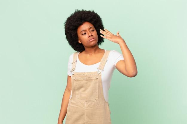 Afro-vrouw voelt zich gestrest, angstig, moe en gefrustreerd, trekt aan de nek van het shirt, ziet er gefrustreerd uit met het concept van de probleemchef