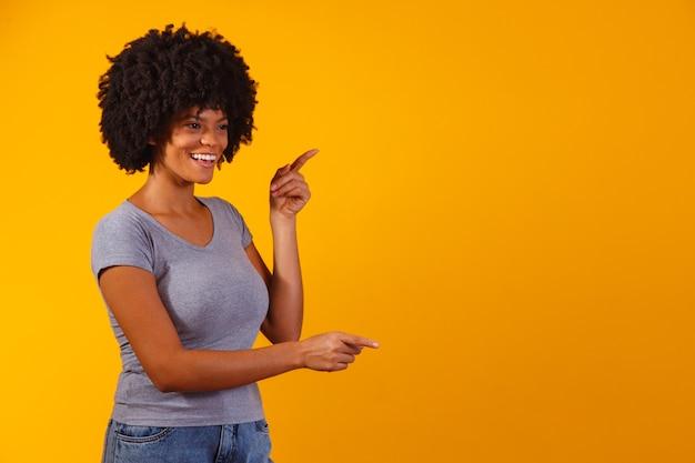 Afro-vrouw wijzend op geel met ruimte voor de tekst Premium Foto