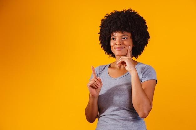 Afro-vrouw wijzend op geel met ruimte voor de tekst