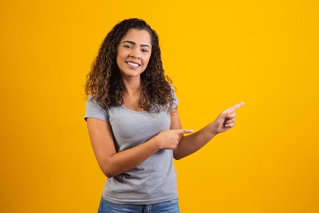 Afro-vrouw wijzend op gele achtergrond met ruimte voor de tekst