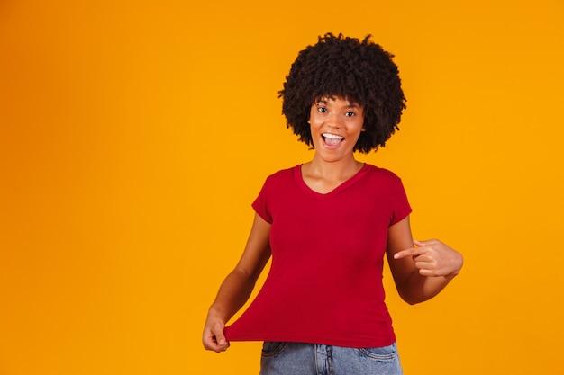Afro vrouw wijzend op t-shirt met ruimte voor tekst.