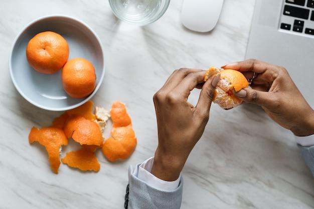 Afro werknemer vrouw handen peeling rijpe zoete mandarijn, blazer dragen, zittend aan een bureau op het werk