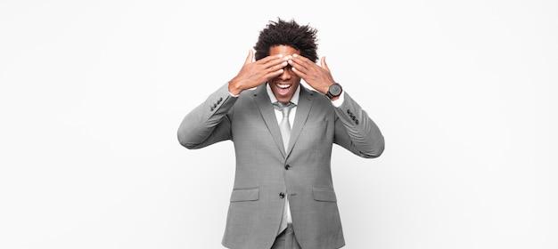 Afro-zakenman glimlacht en voelt zich gelukkig, bedekt de ogen met beide handen en wacht op een ongelooflijke verrassing